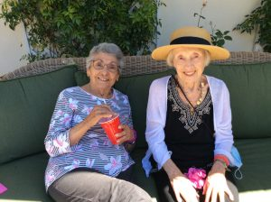 two senior ladies enjoying root beer floats on the patio of Wood Glen Hall Assisted Living