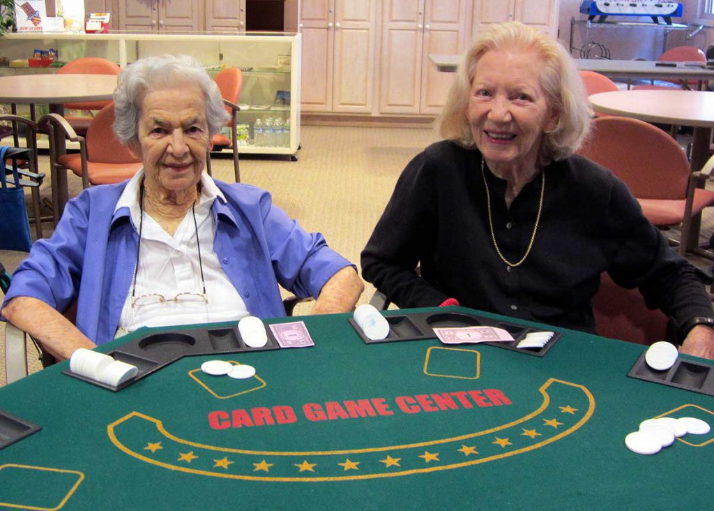 Two senior women playing blackjack at Wood Glen Hall Assisted Living
