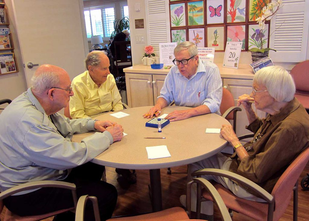 A group of seniors playing Boggle at Wood Glen Hall Assisted Living