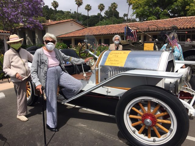 Car Parade Santa Barbara Retirement Community two women checking out a 1915 car