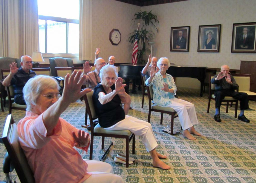 A group of seniors enjoying Chair Tai Chi at Wood Glen Hall Assisted Living
