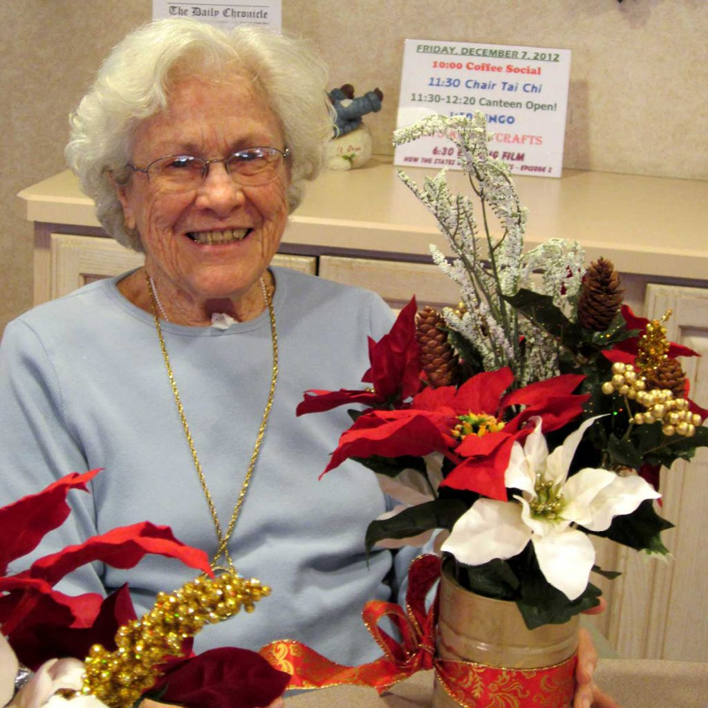 A senior woman crafting Poinsettias at Wood Glen Hall Assisted Living