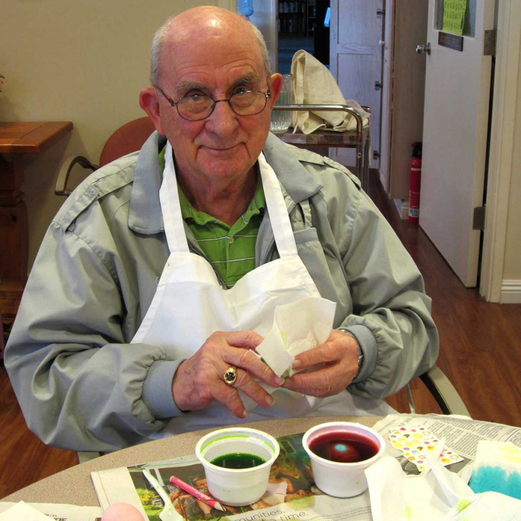 a senior man painting Easter Eggs at Wood Glen Hall Assisted Living