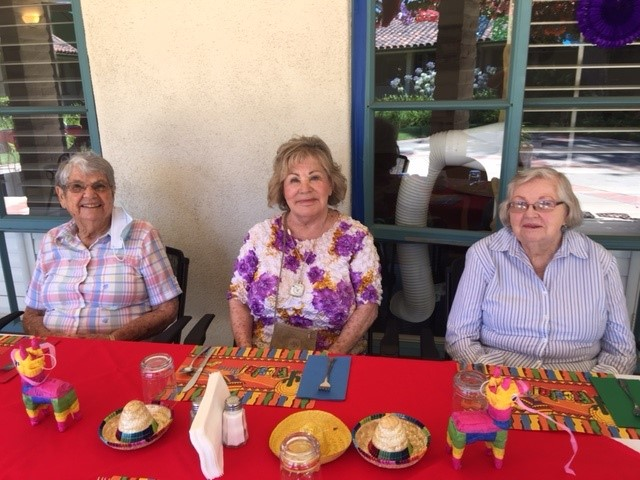 Three residents of Wood Glen Hall about to enjoy the Fiesta lunch on the patio