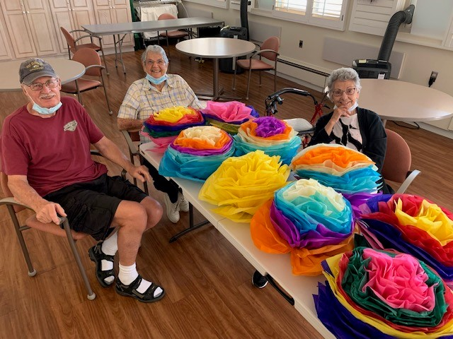 residents of Wood Glen Hall with completed tissue paper flower craft
