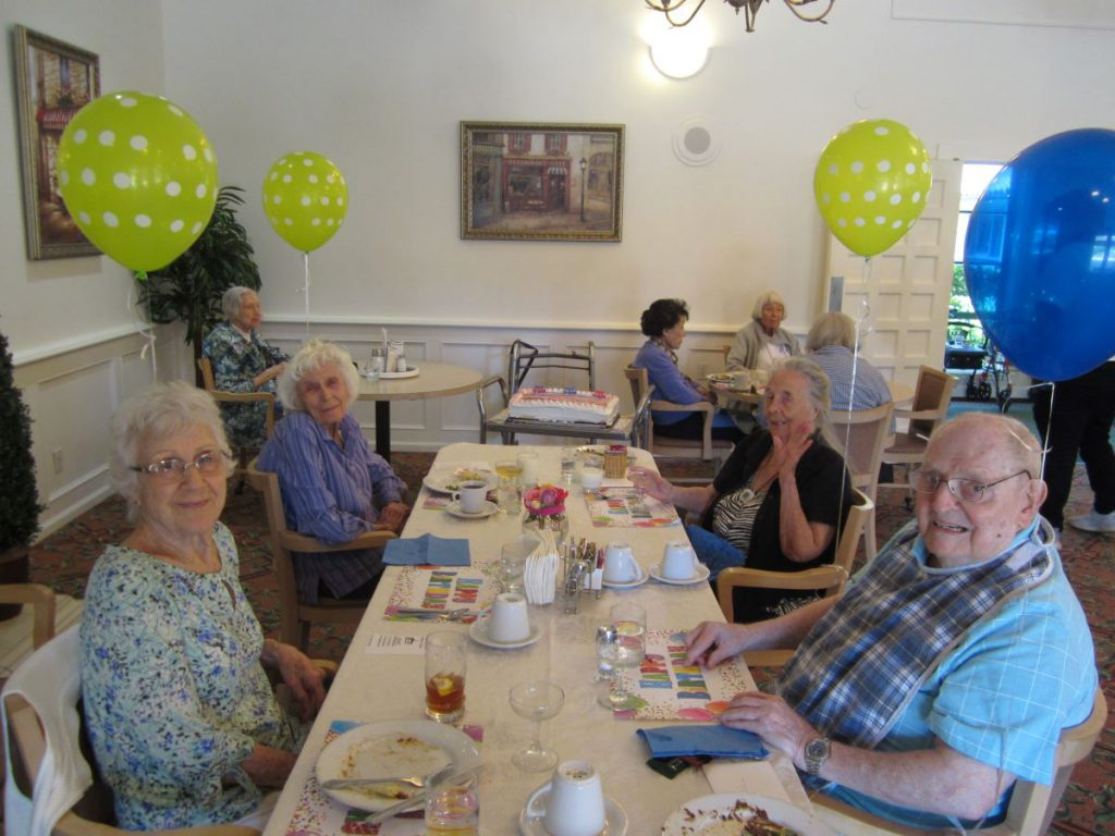 Four senior residents of a Santa Barbara Assisted Living Community, Wood Glen Hall, enjoying their birthday celebration in the Dining Room