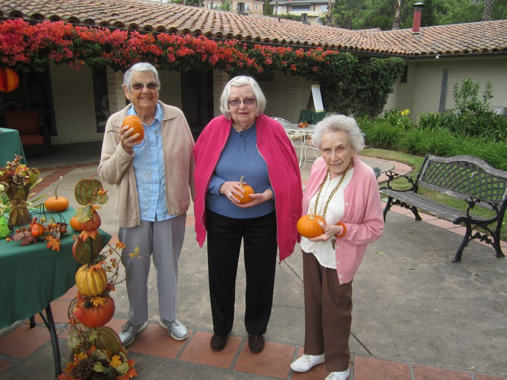 three Santa Barbara assisted living residents holding pumpkins at the Wood Glen Hall mini pumpkin patch