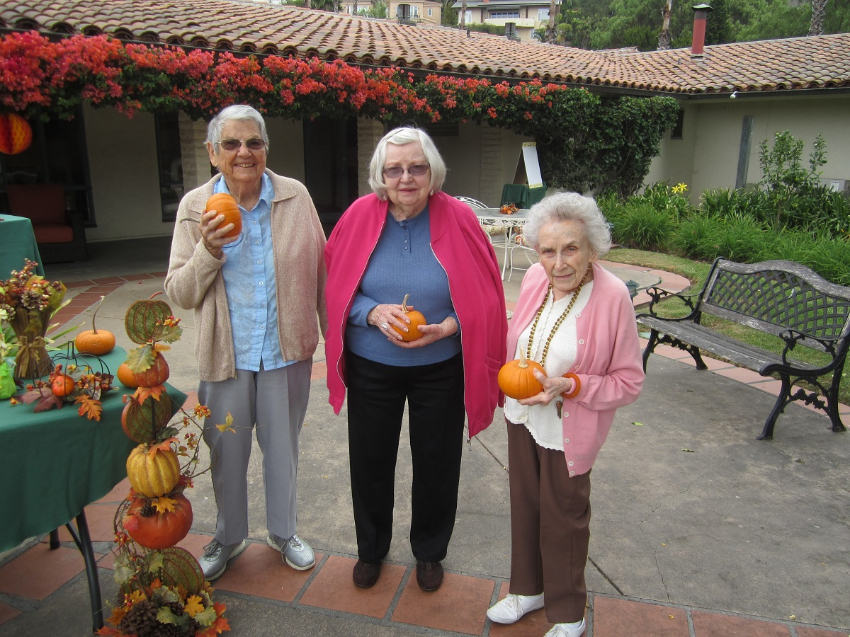 three Santa Barbara assisted living residents holding pumpkins at the Wood Glen Hall mini pumpkin patch