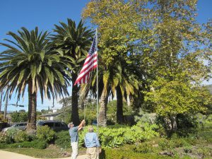 two men raising new American flag at Assisted living community in Santa Barbara