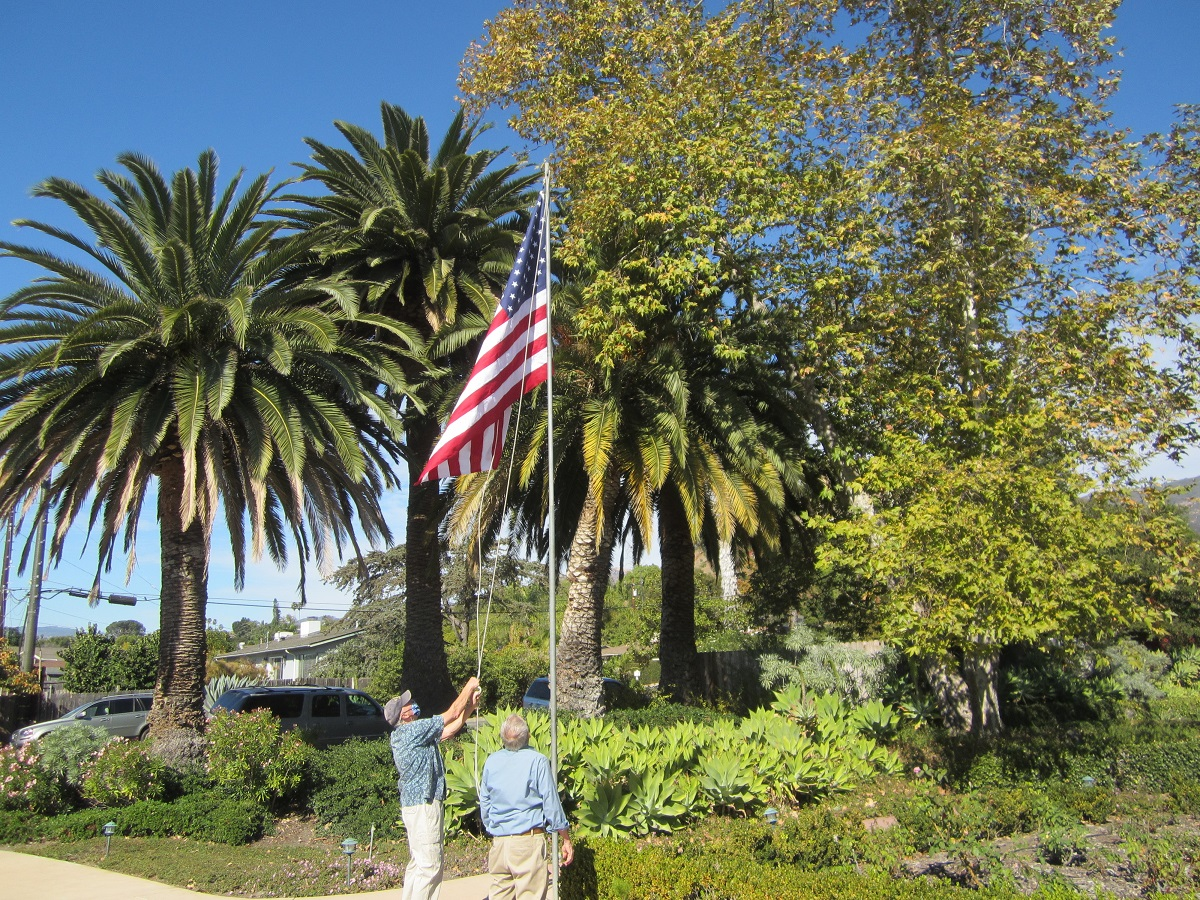 two men raising new American flag at Assisted living community in Santa Barbara