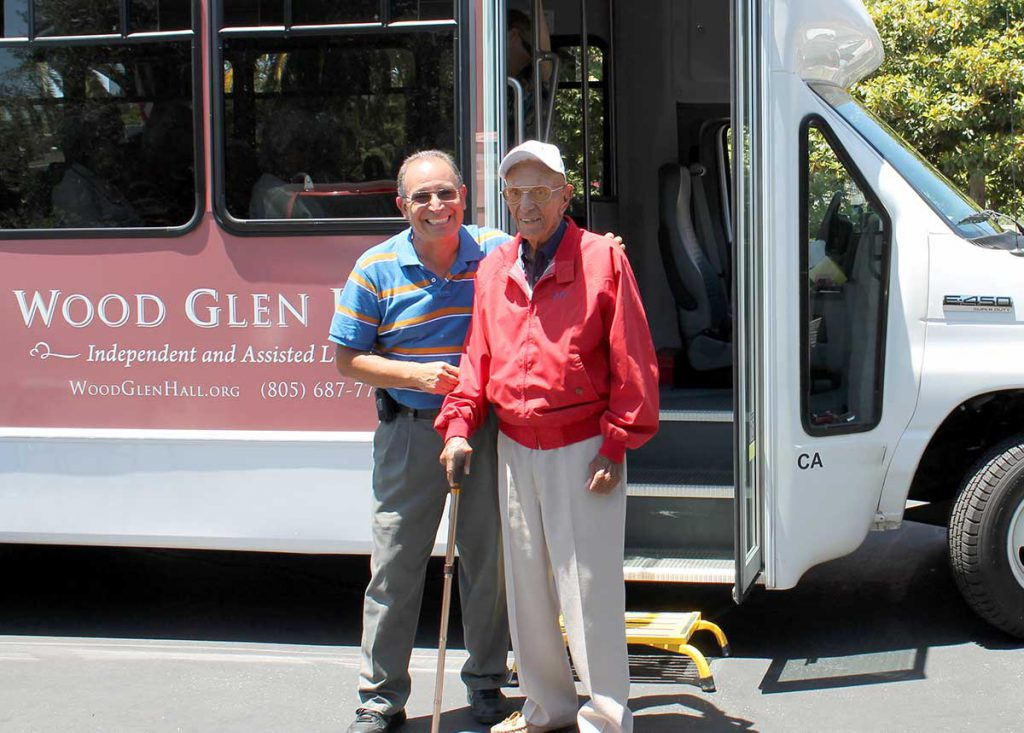 A bus driver helping a resident off the bus at Wood Glen Hall Assisted Living in Santa Barbara