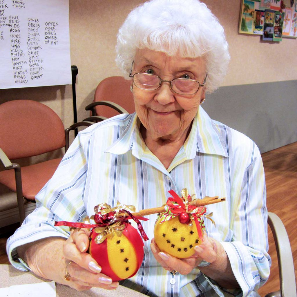 A senior woman making crafts at Wood Glen Hall Assisted Living