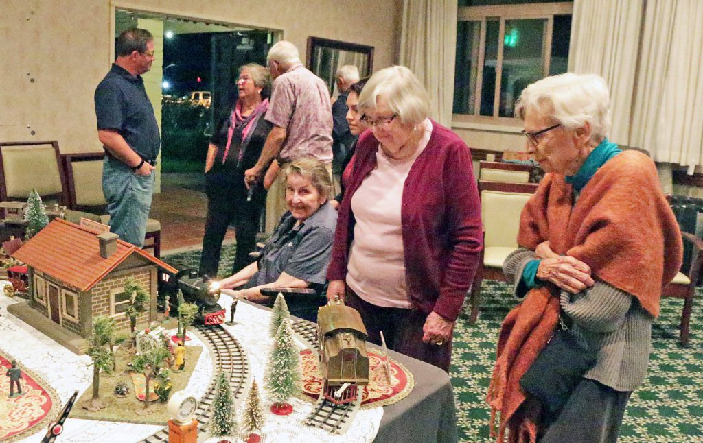 Three senior citizen residents of Wood Glen Hall Independent and Assisted Living in Santa Barbara, California, observe a toy train at the display set up by the Coast Toy Train Club