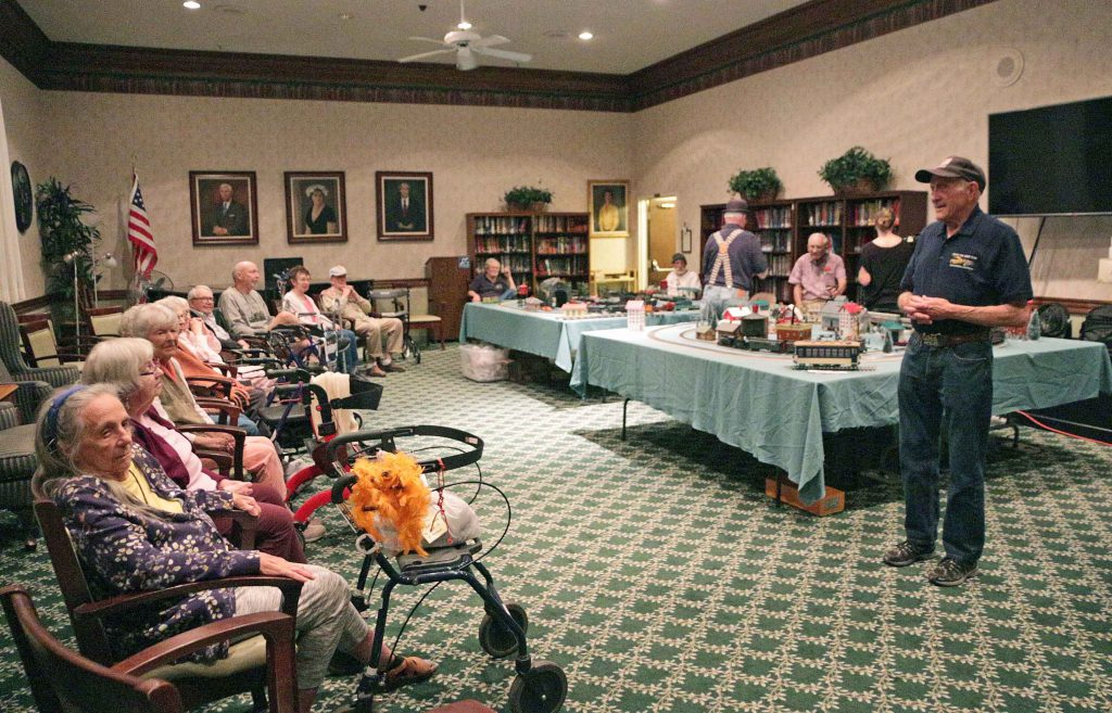 Members of the Coast Toy Train Club speak to the senior citizen residents of Wood Glen Hall Independent and Assisted Living about the toy train display they have set up