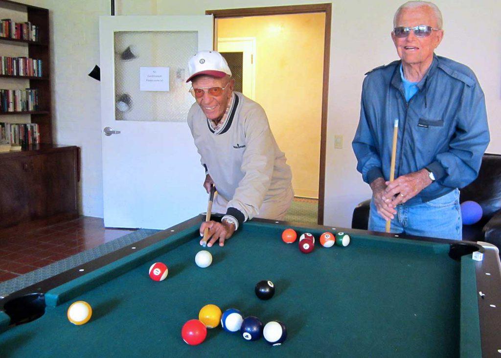 Two senior gentlemen enjoying pool at Wood Glen Hall Assisted Living