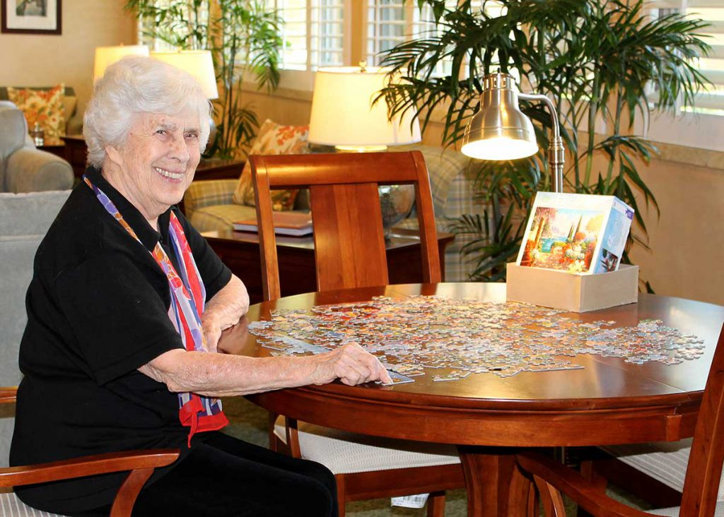 Enjoying a puzzle on the Lanai at Wood Glen Hall Assisted Living