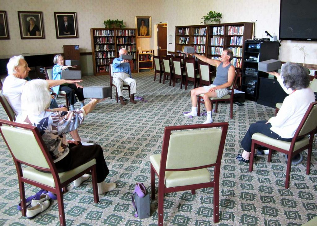 Yoga class with Daniel in chairs at Wood Glen Hall Assisted Living