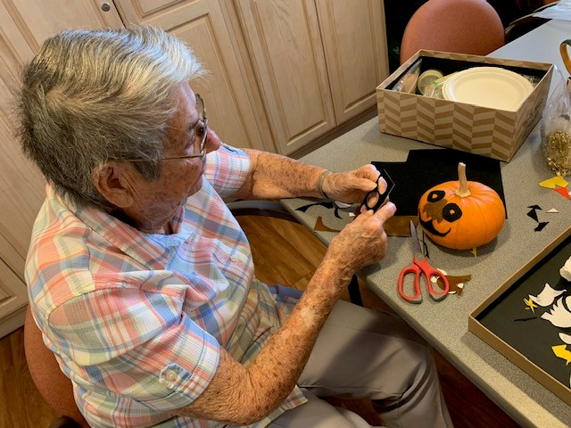 senior resident decorating pumpkins