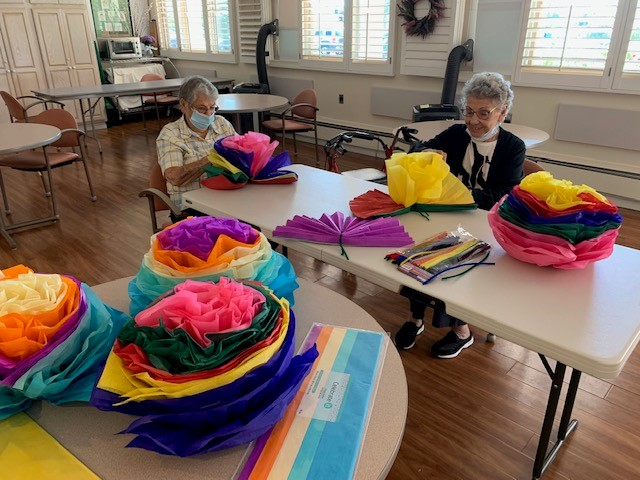 residents of Wood Glen Hall working on tissue paper flower craft